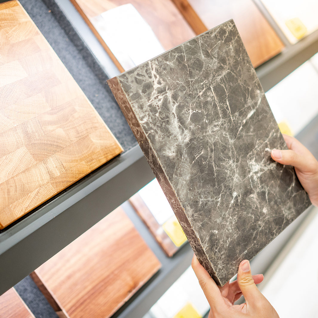 Male hand choosing cabinet panel materials or countertops for built-in furniture design. Shopping furniture and decoration. Home improvement concept